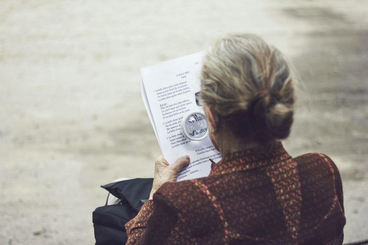 ηλικιωμένη γυναίκα διαβάζει εφημερίδα με μεγενθυντικό φακό και έχει αυξημένο κίνδυνο για άνοια