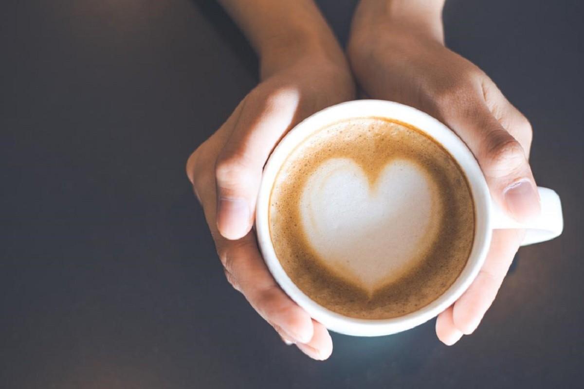 γυναικεία χέρια κρατούν μια κούπα στην οποία υπάρχει καφές