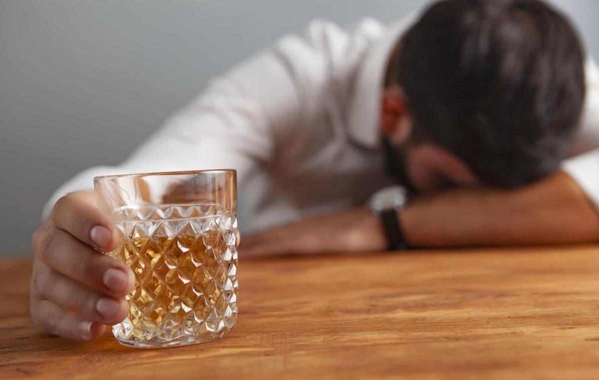 άνδρας κρατάει ένα ποτήρι με αλκοόλ