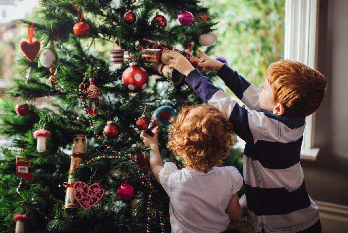 παιδιά στολίζουν το δέντρο για τα Χριστούγεννα