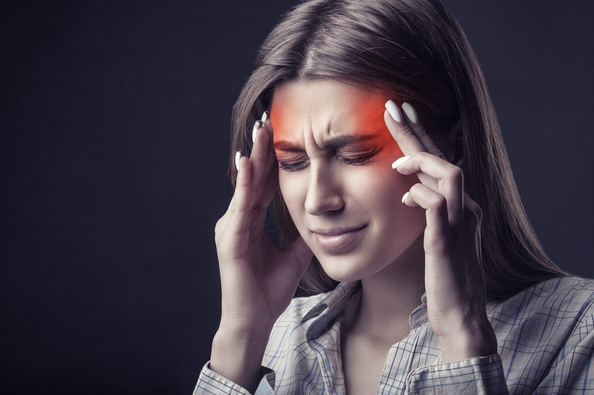 γυναίκα κρατά το κεφάλι της από τον πονοκέφαλο και την ημικρανία