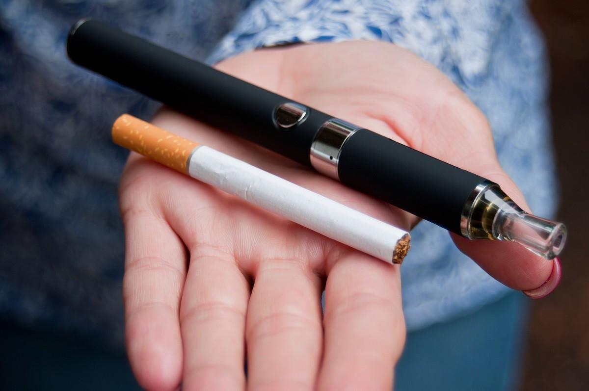 γυναικείο χέρι κρατά κανονικό και ηλεκτρονικό τσιγάρο