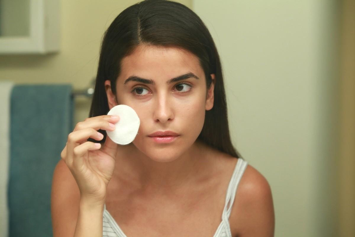 νεαρή γυναίκα βγάζει το μακιγιάζ της