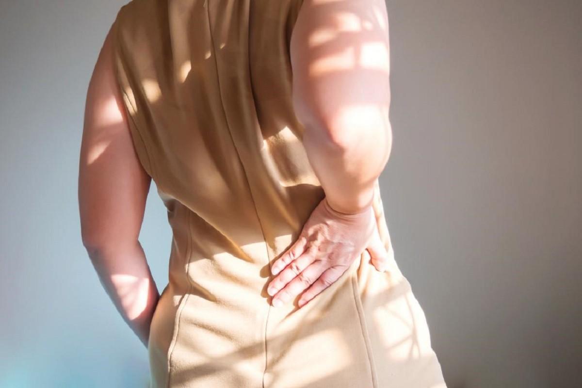 γυναίκα κρατά τη μέση της επειδή έχει πόνους στα νεφρά