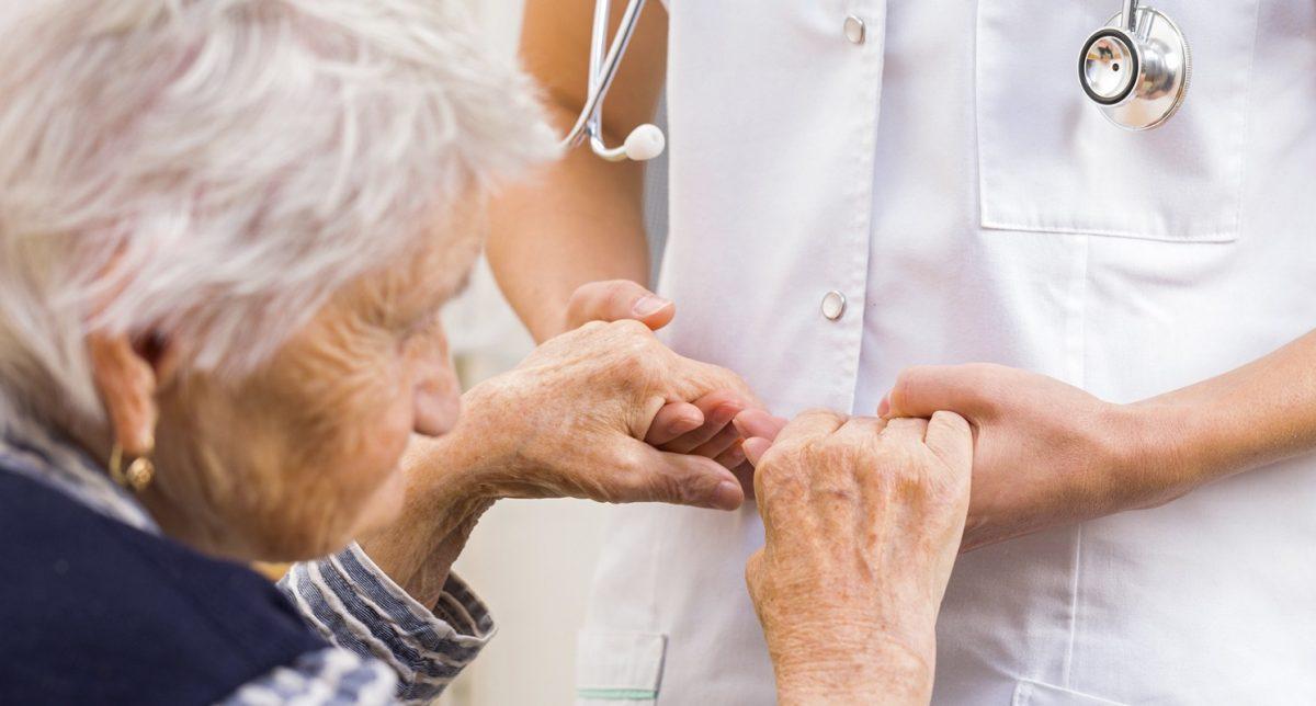 γιατρός κρατάει τα χέρια ηλικιωμένης γυναίκας με Πάρκινσον