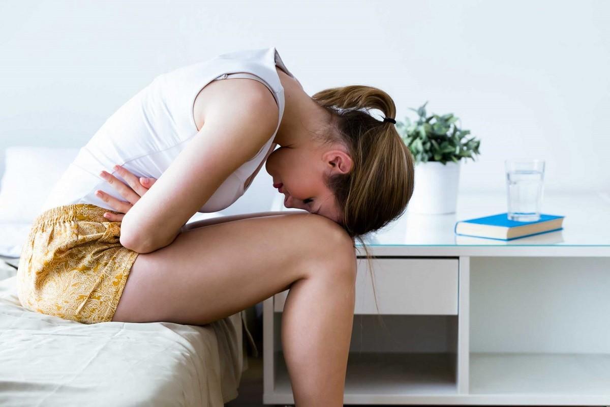 Γυναίκα που την πονάει η κοιλιά της από την δυσκοιλιότητα