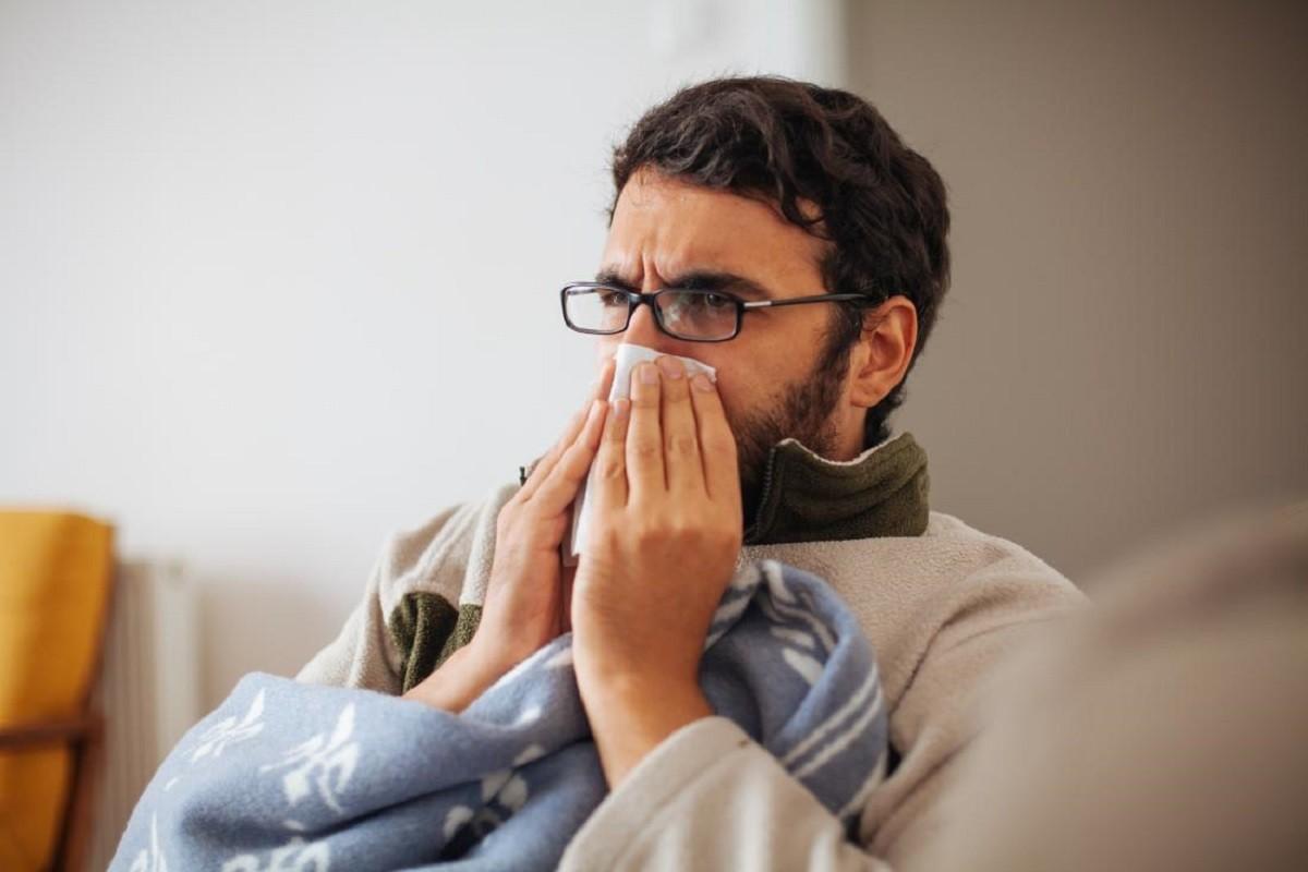 άνδρας φυσάει τη μύτη του από κρυολόγημα