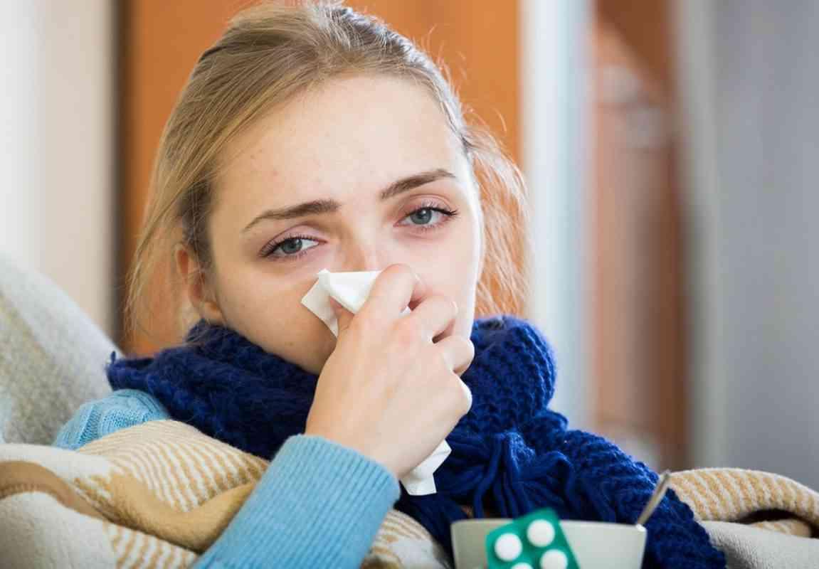 κοπέλα με κρυολόγημα φυσάει τη μύτη της