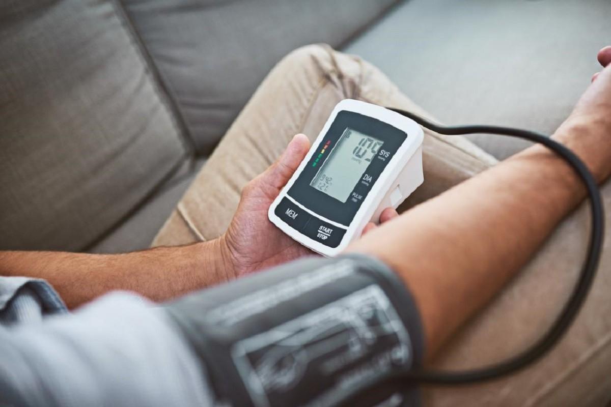 άνδρας μετράει την πίεση του με πιεσόμετρο για να δει αν έχει υπέρταση ή υπόταση