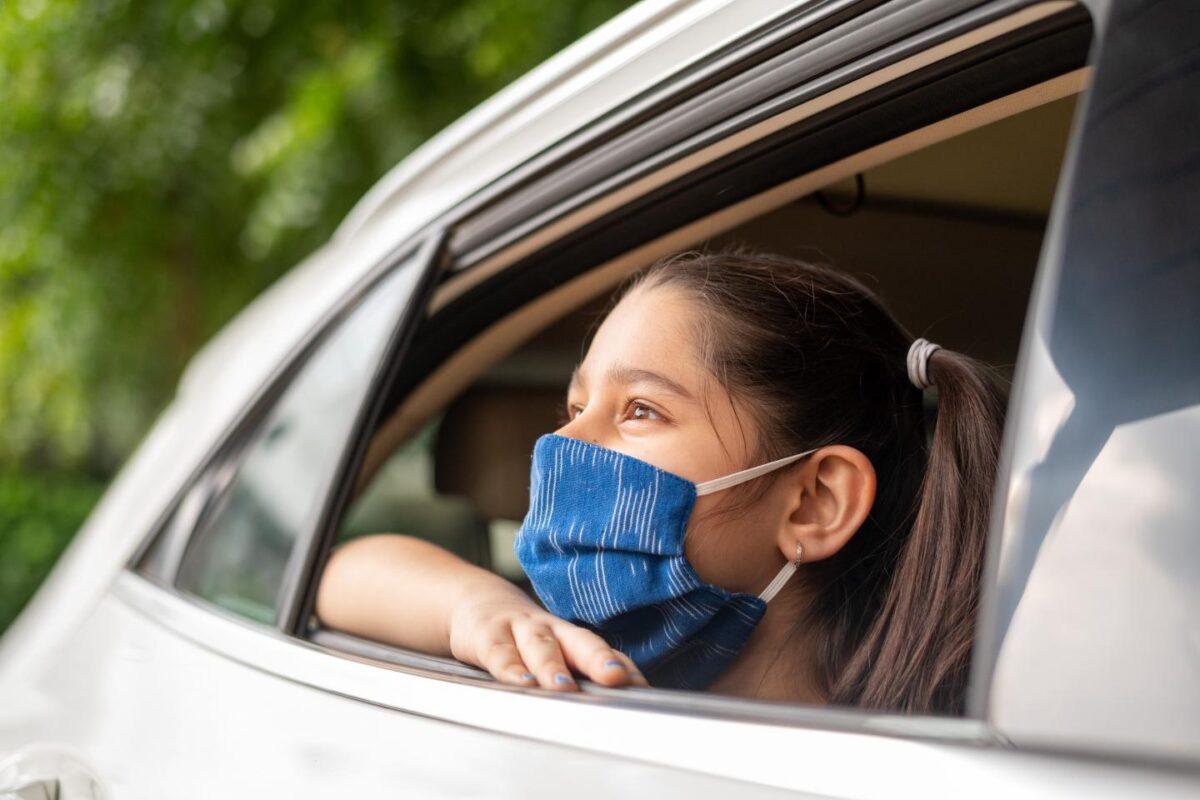 κοριτσάκι μέσα στο αυτοκίνητο φοράει μάσκα για να μην την μολύνει ο κορωνοϊός