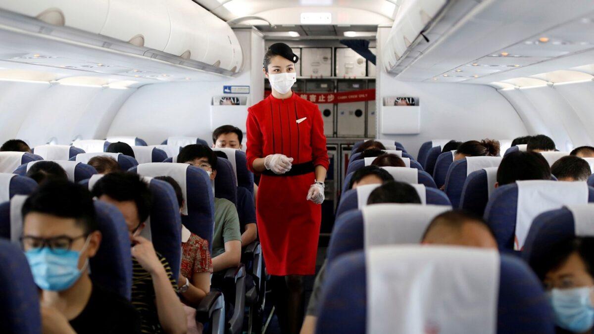 επιβάτες φορούν μάσκες για να μην μεταδοθεί ο κορωνοϊός στο αεροπλάνο