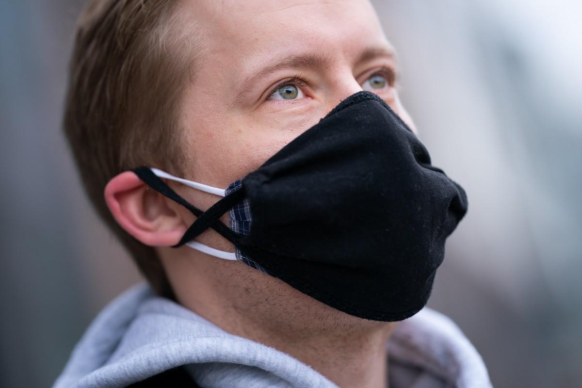 άντρας φοράει διπλή μάσκα για να μην τον μολύνει ο κορωνοϊός