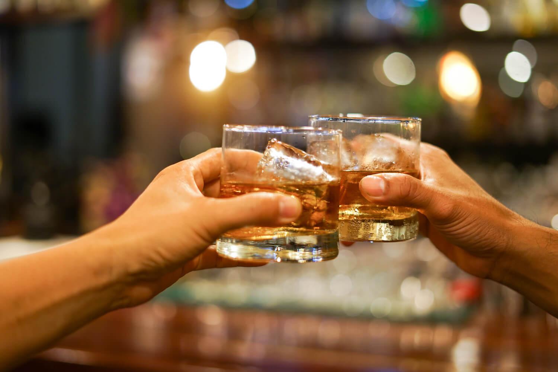 Άνδρες τσουγκρίζουν δυο ποτήρια με αλκοόλ