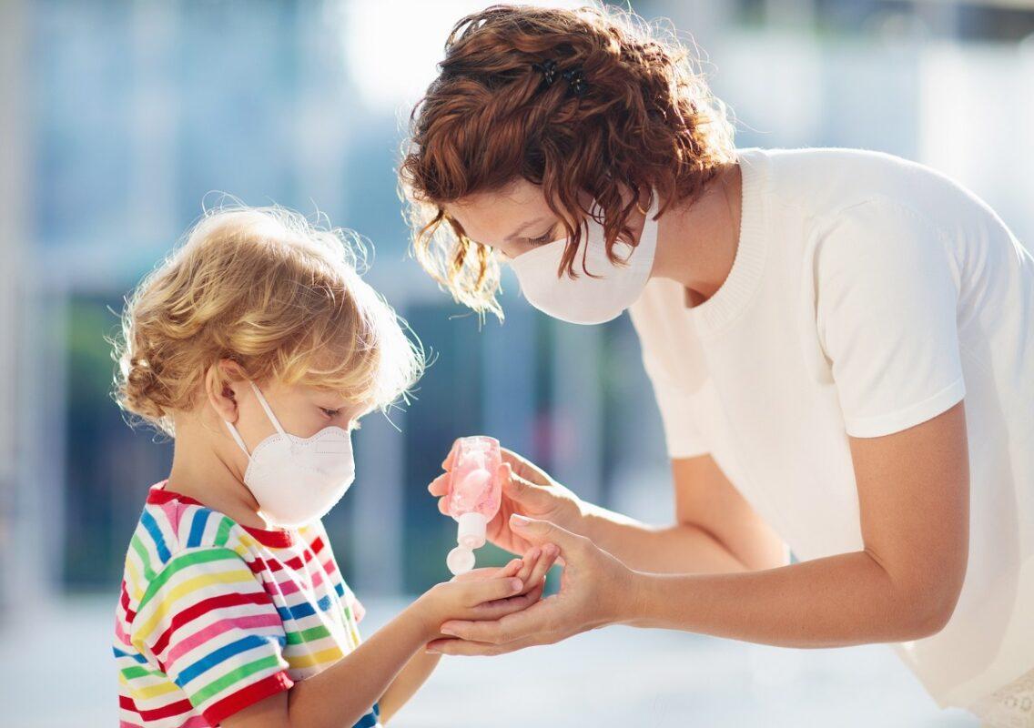 παιδί φορά μάσκα και βάζει αντισηπτικό για να μην το μολύνει ο κορωνοϊός