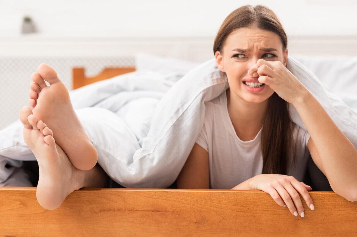 γυναίκα κρατά την μύτη της γιατί τα πόδια δίπλα της μυρίζουν άσχημα