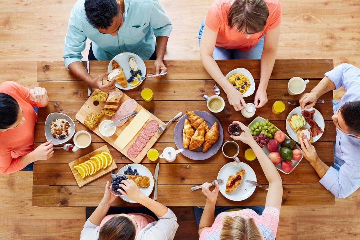 οικογένεια κάθεται στο τραπέζι και τρώει πρωινό