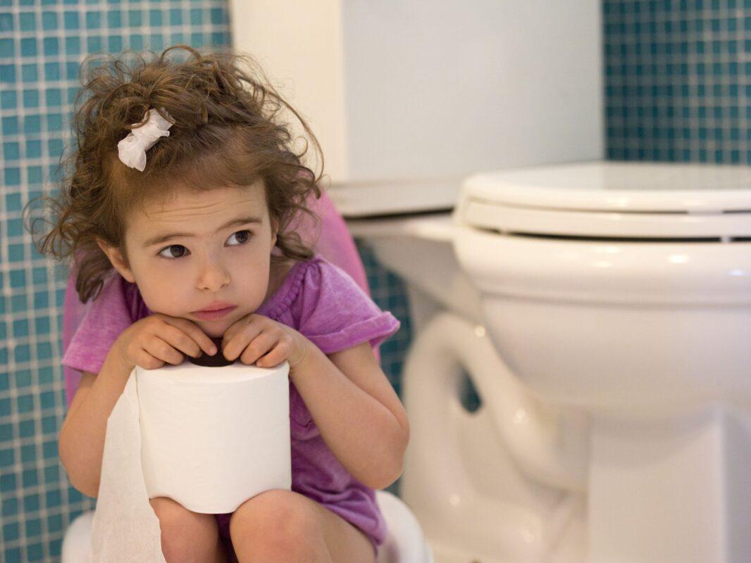 κοριτσάκι στην τουαλέτα κρατά χαρτί υγείας