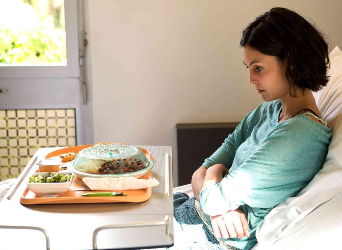 γυναίκα που κοιτάει το φαγητό της και δεν θέλει να φάει επειδή έχει ανορεξία