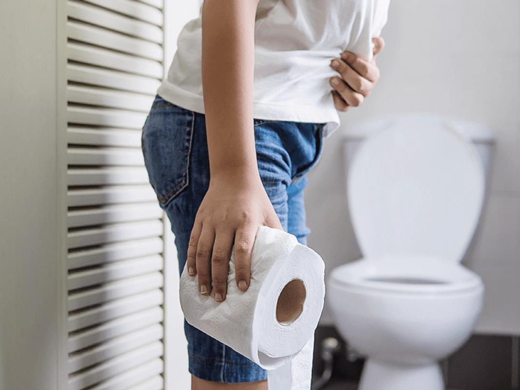 άνδρας με δυσκοιλιότητα στην τουαλέτα κρατά ένα χαρτί υγείας